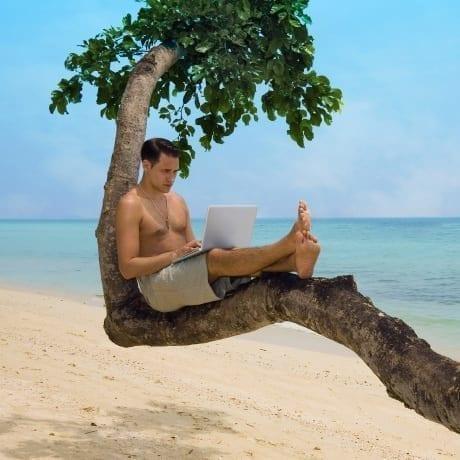 Homme avec un ordinateur sur une grosse branche d'arbre devant la plage