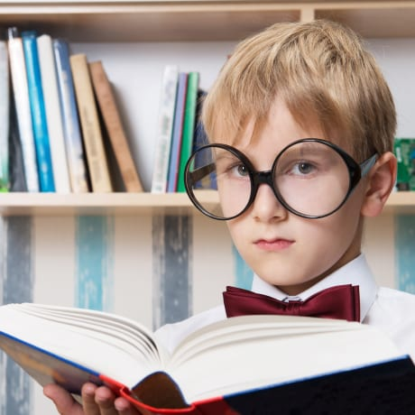 Enfant et gros dictionnaire avec des grosses lunettes