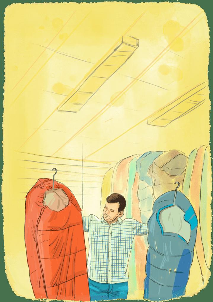 Homme qui choisit un sac de couchage pour faire le tour du monde dans un magasin