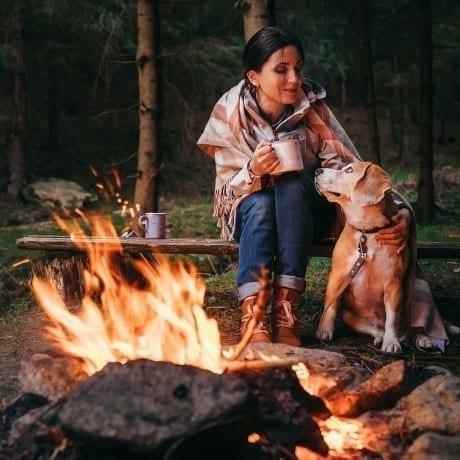 Femme avec son chien devant un feu de camp